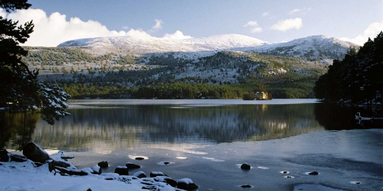 An icy loch shore with snowy mountains on the far side