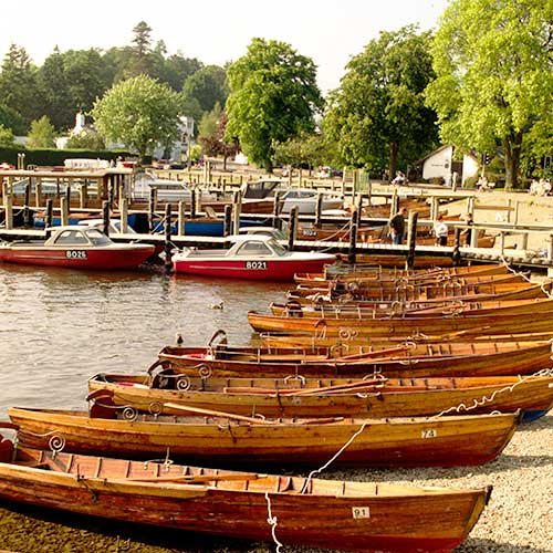 Wooden rowing boats tied on the shingle shore of a lake