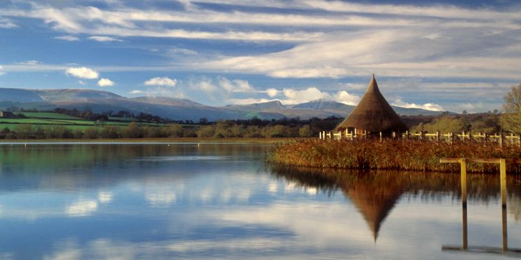 A thatched roundhouse reflected in a lake