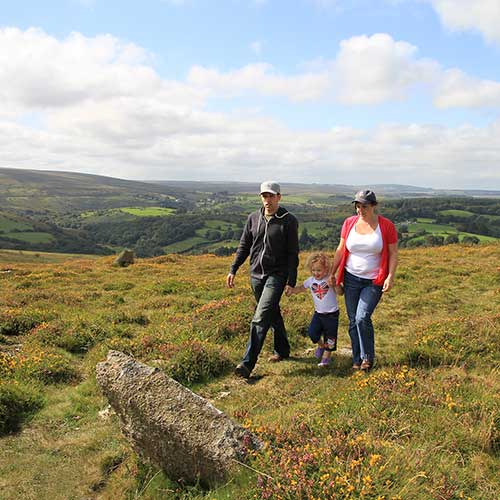 Parents and a young girl holding hands as they walk over moorland