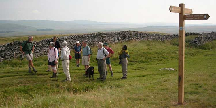 Group of walkers by a wooden signpost with view over the valley below