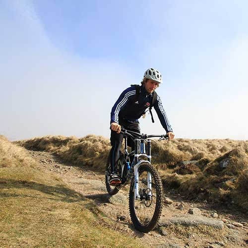 A mountain biking descending a steep stony path