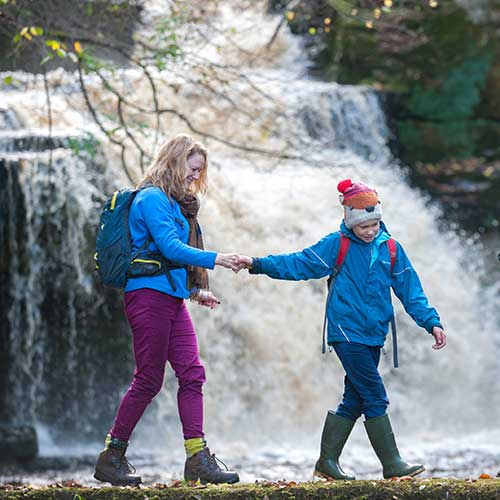 A mother and child walking along a path with a gushing waterfall behind them