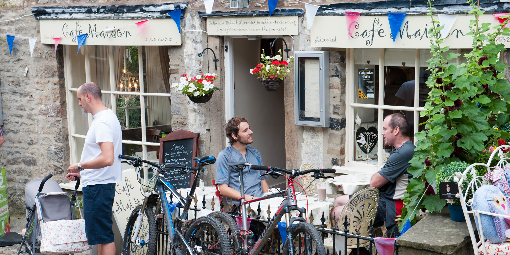 Cyclists relaxing outside a cafe hung with colourful bunting