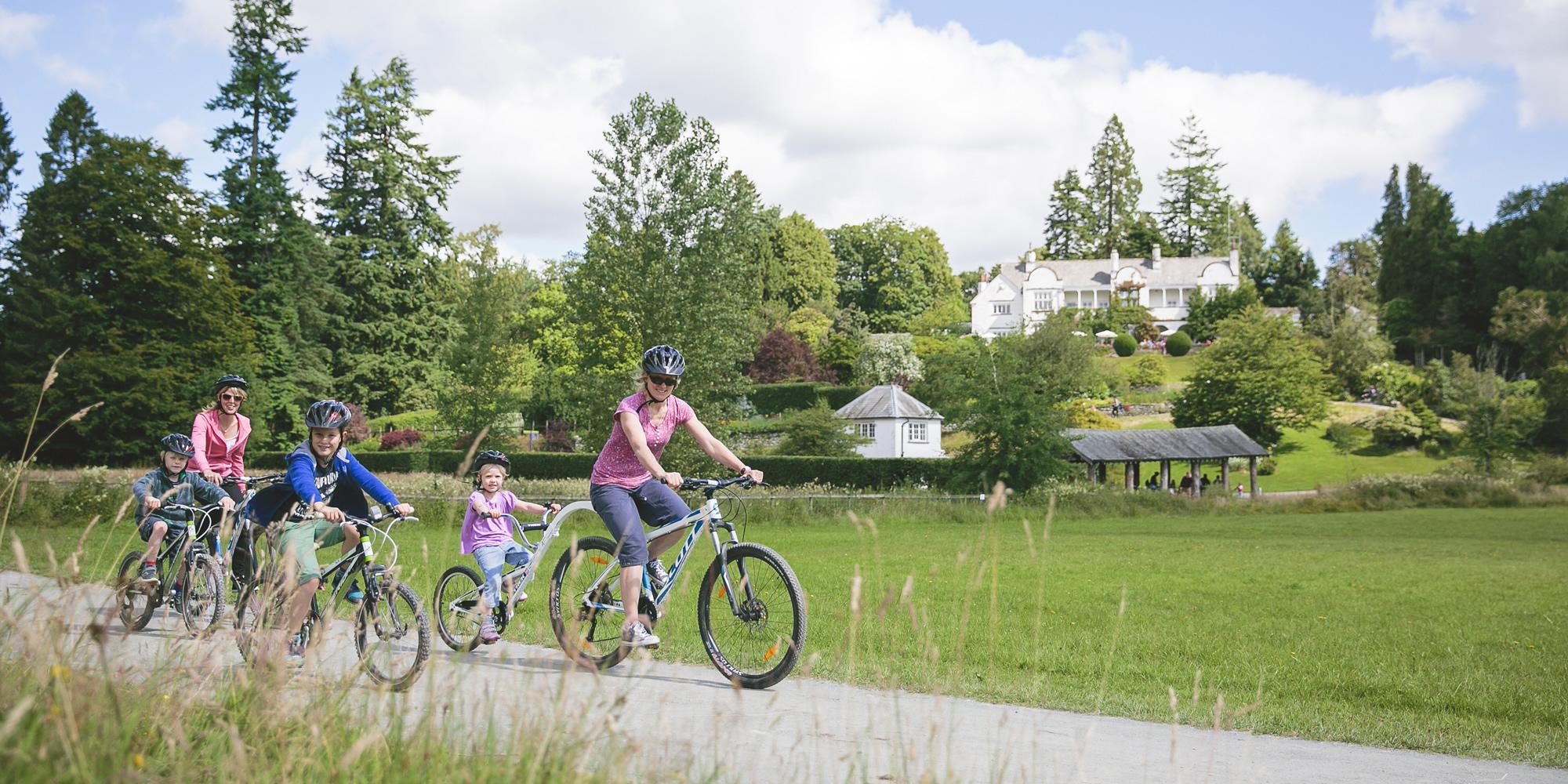 Family cycling through gardens