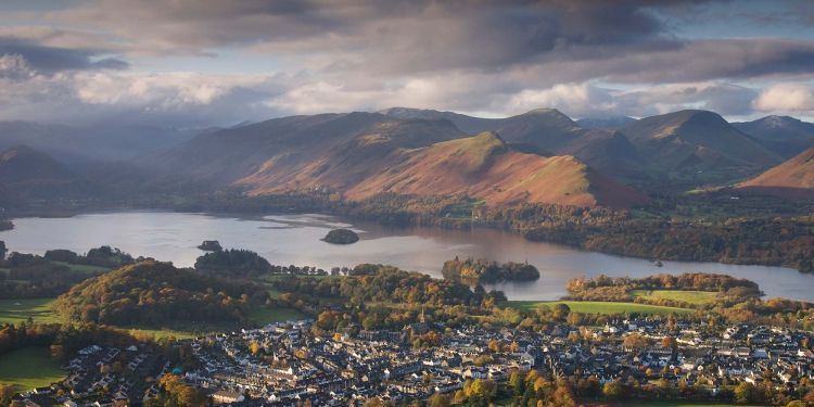 View over a lake nestled between high fells with a town on the near shore