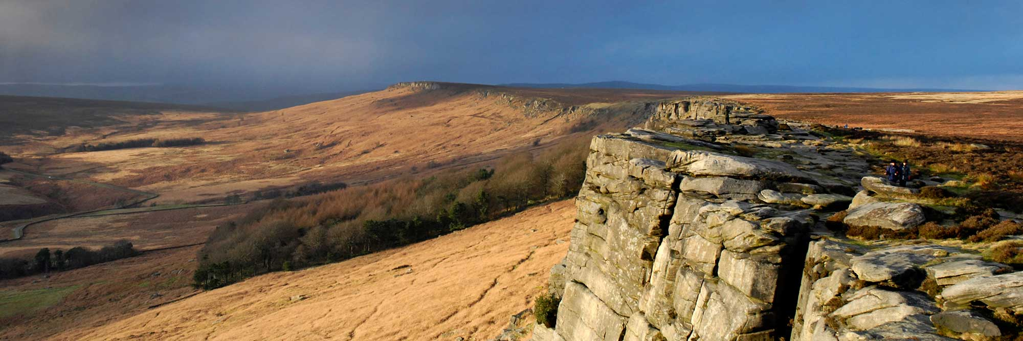 A long sheer cliff face, with moorland below
