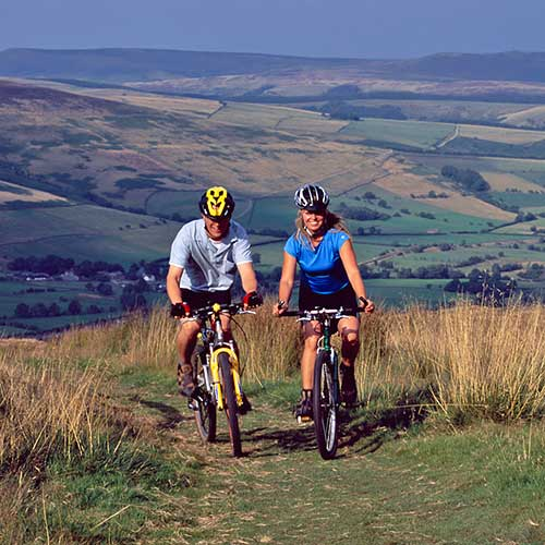 Two people mountain biking on a grassy track with a valley below