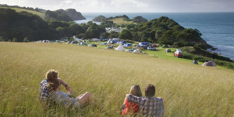 Two couples sitting in long grass looking down on a campsite next to a sea cliff