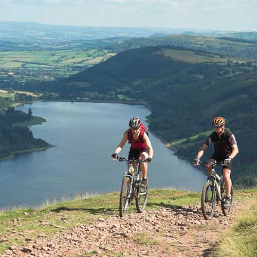 Two people mountain biking on a grassy mountain side above a reservoir