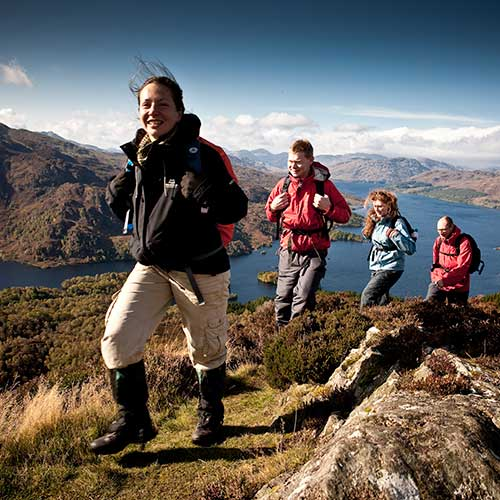 A group of walkers on a mountain side with a loch below