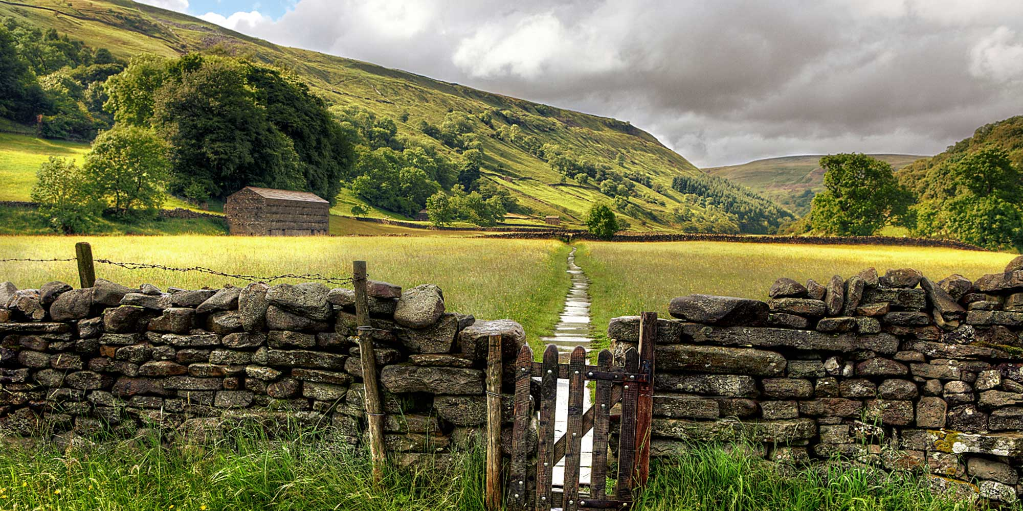 A gate in a stone wall, with a path across a flower meadow stretching into the distance
