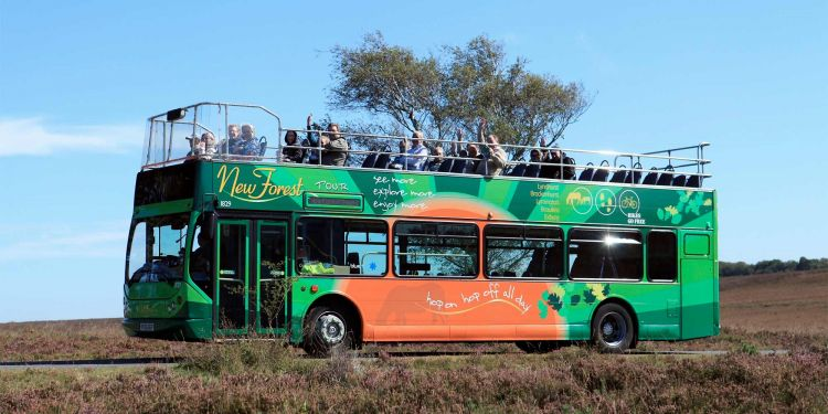 Open bus with visitors enjoying a view across open moorland
