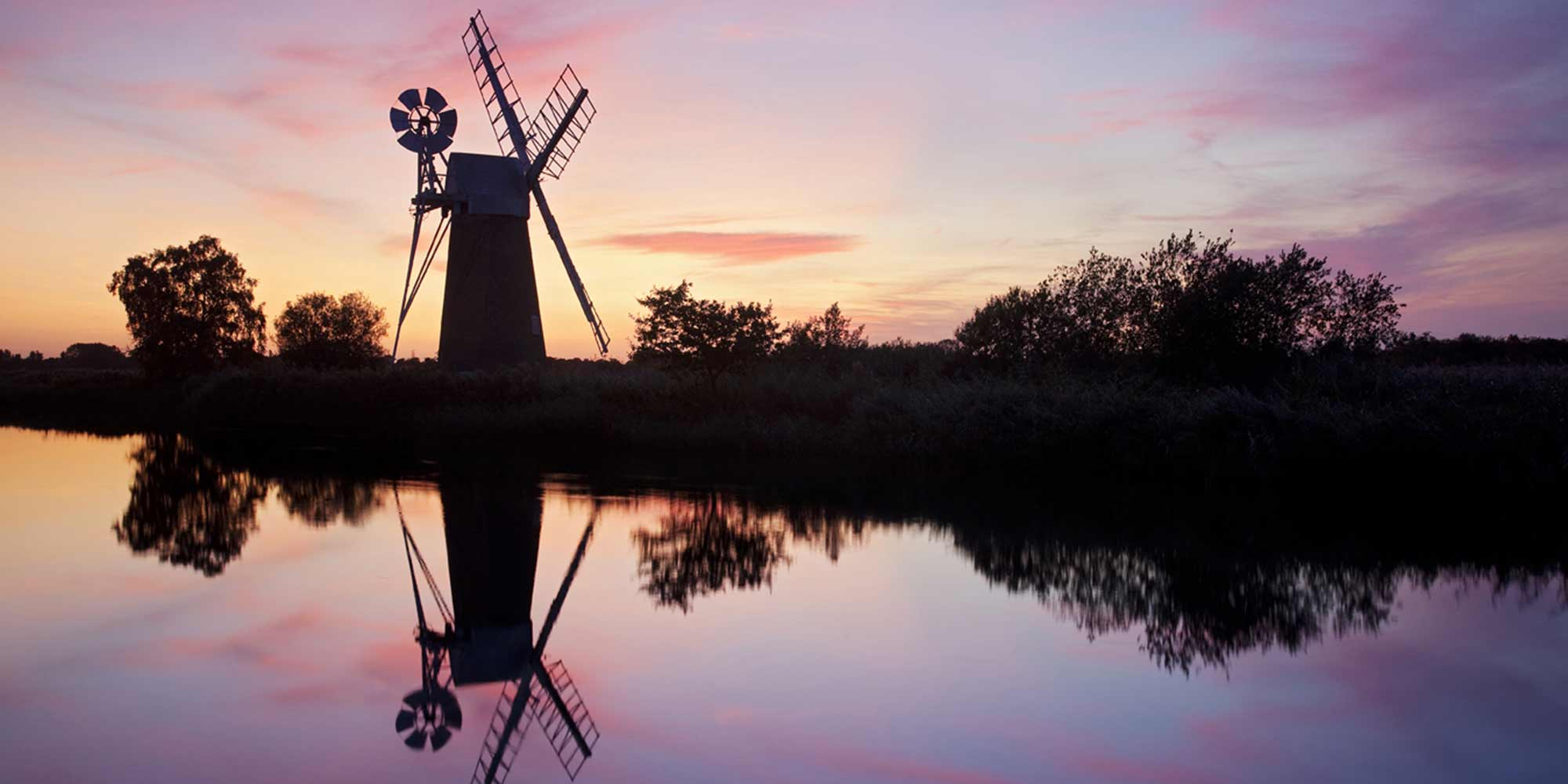A windmill silhouetted against a pink sky and reflected in a river