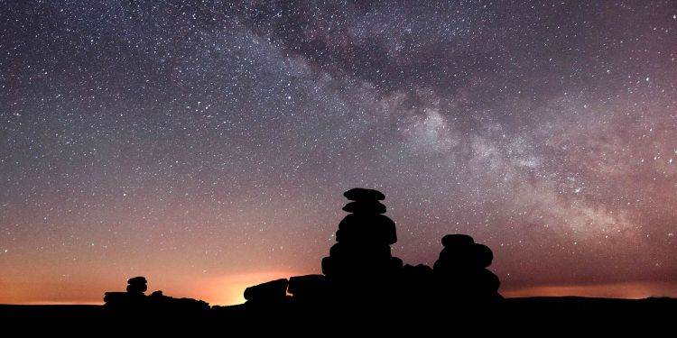 A star filled sky above silhouette of rocky outcrops