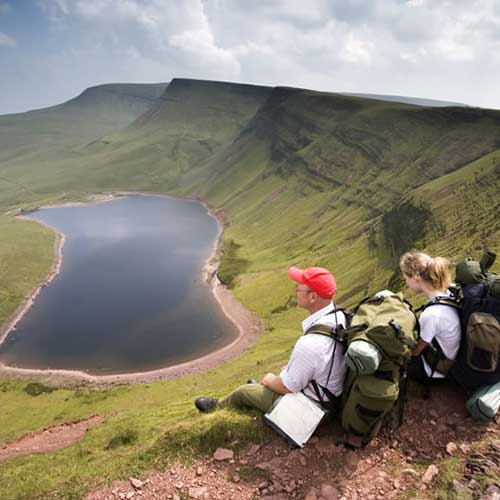 Walkers resting on a mountain side overlooking a mountain lake below