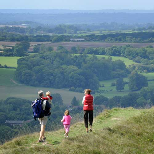 A family with young children walking along a hilltop path with views over trees and fields for miles below