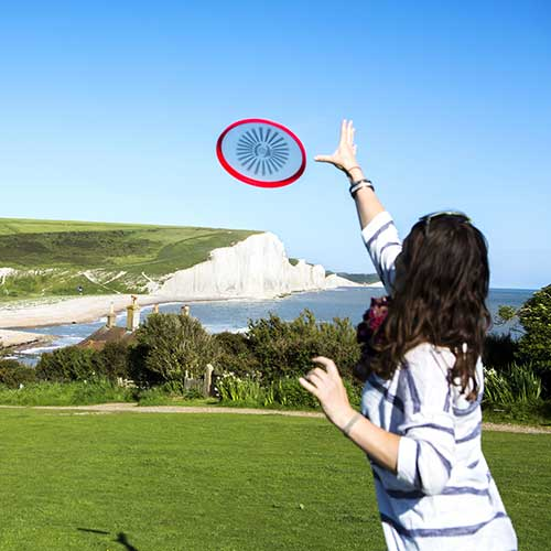 A girl throwing a frisbee with chalk sea cliffs in the background