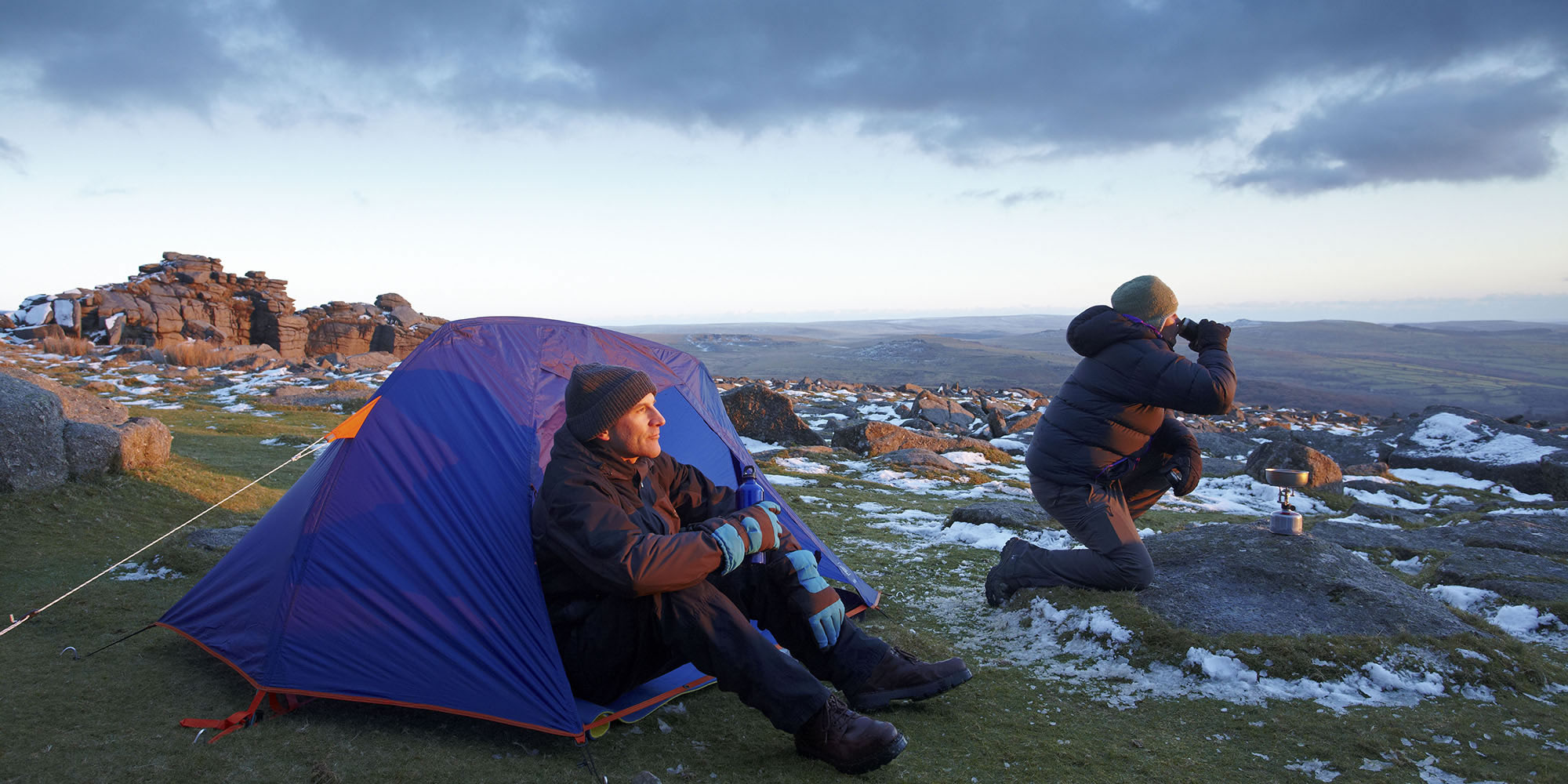 A couple sitting by a tent on a snowy tor