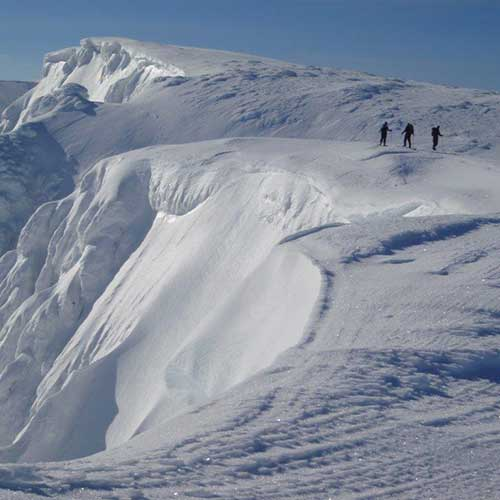 Steep mountains covered in deep snow with a group of walkers on the summit
