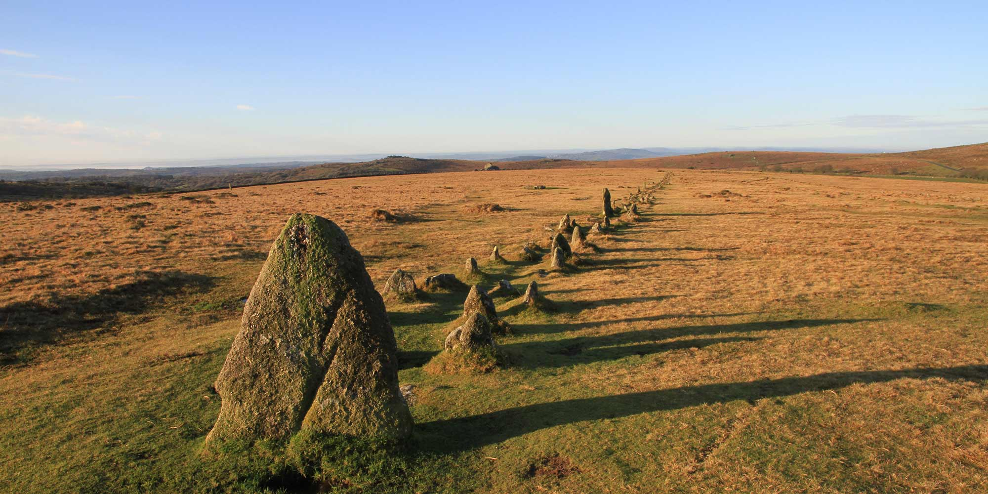 A long row of pre-historic standing stones on grassy moorland