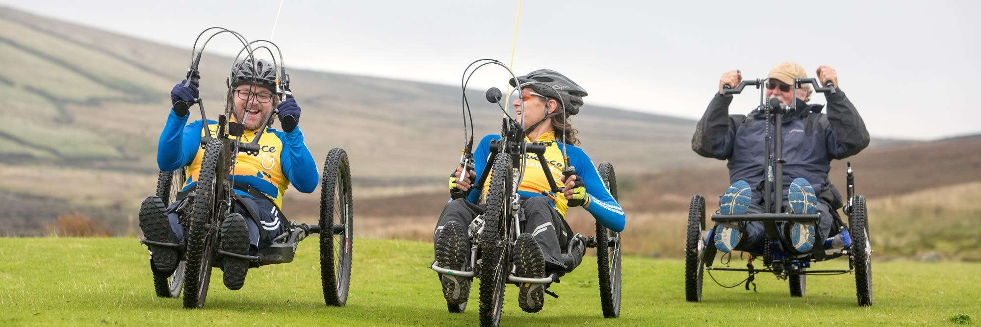 Three visitors on all-terrain hand bikes
