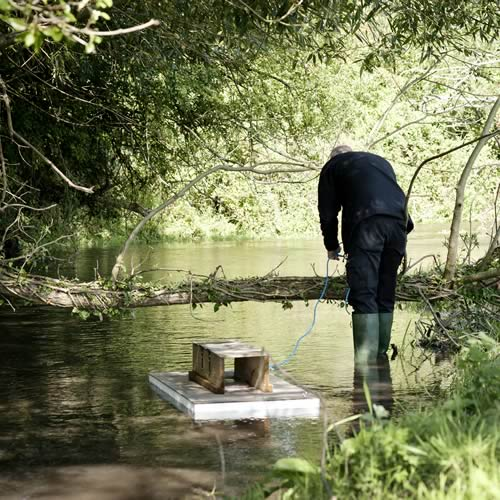 Man in a river with a small wooden raft