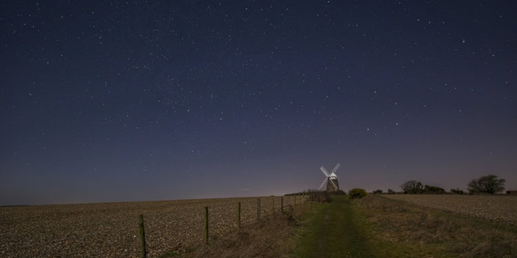 A windmill under a star studded dark sky