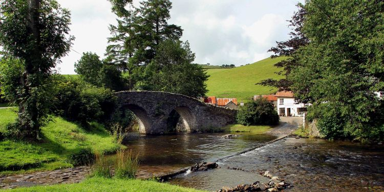 Stone bridge over a river, with a cottage on the far riverbank