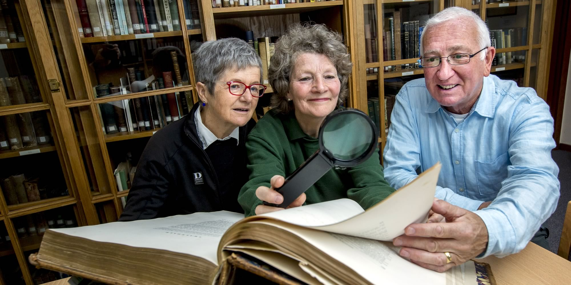 People in a library with old archive books.