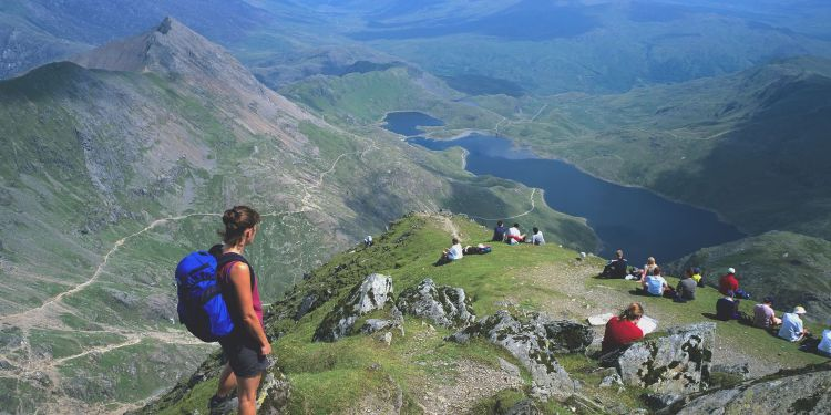 Walkers enjoying a view over tarns and a glacial valley below