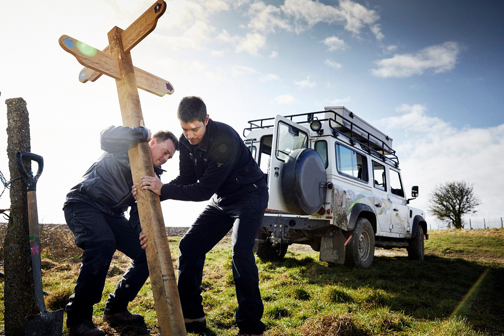Rangers erecting a wooden signpost