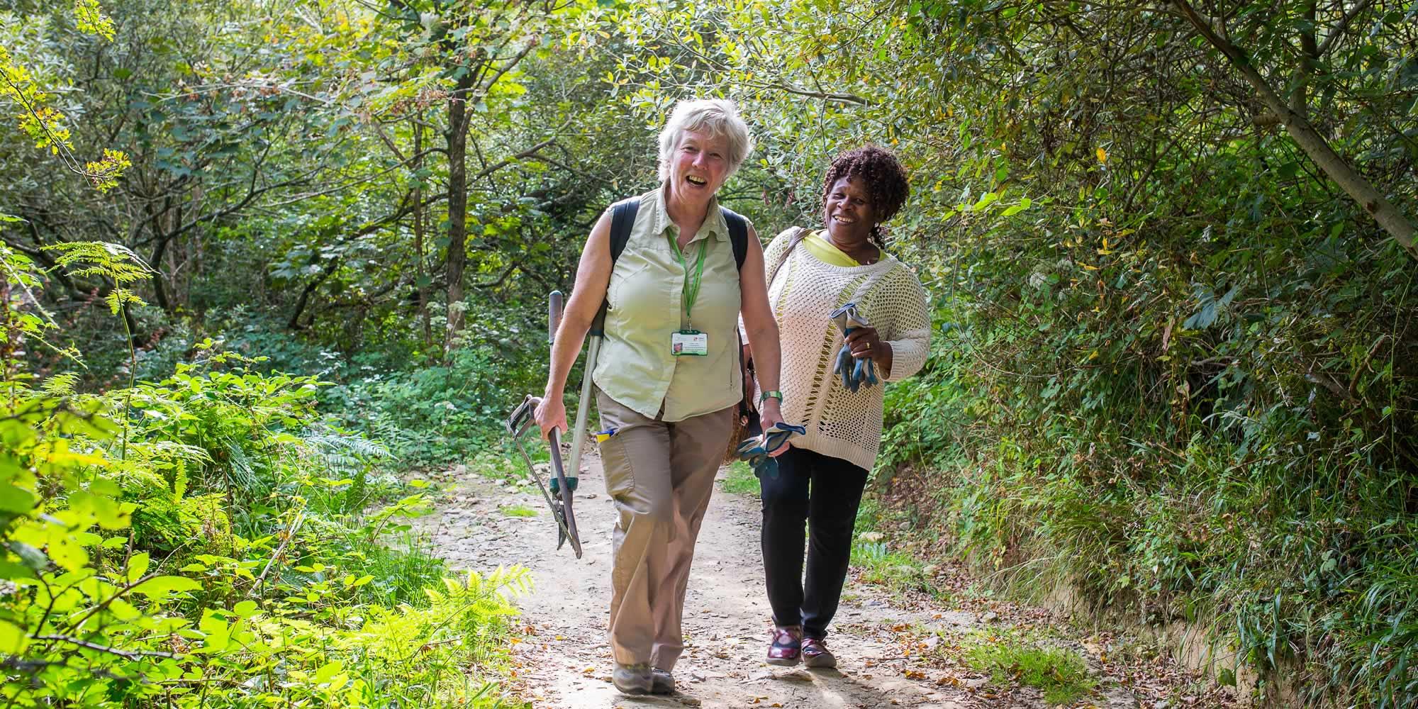 Two women walking through a summer woodland