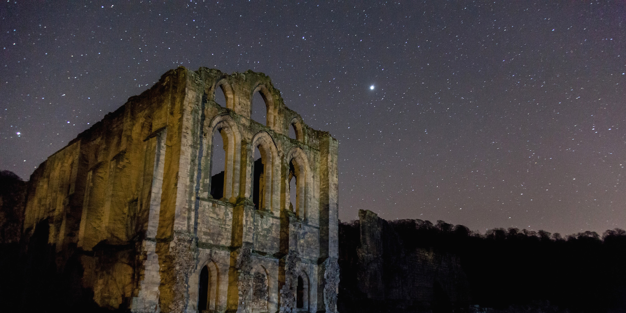 A deep starry sky over a ruined stone abbey