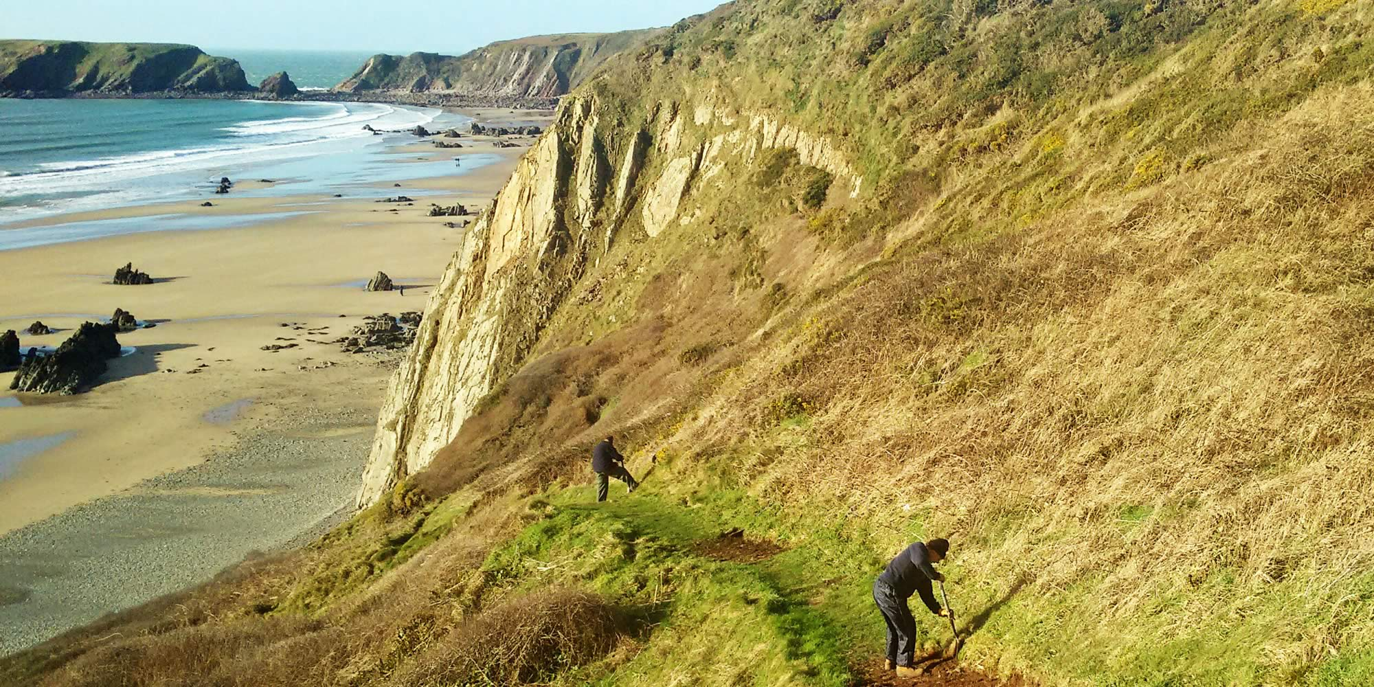 People with spades on a footpath along a high coastal cliff