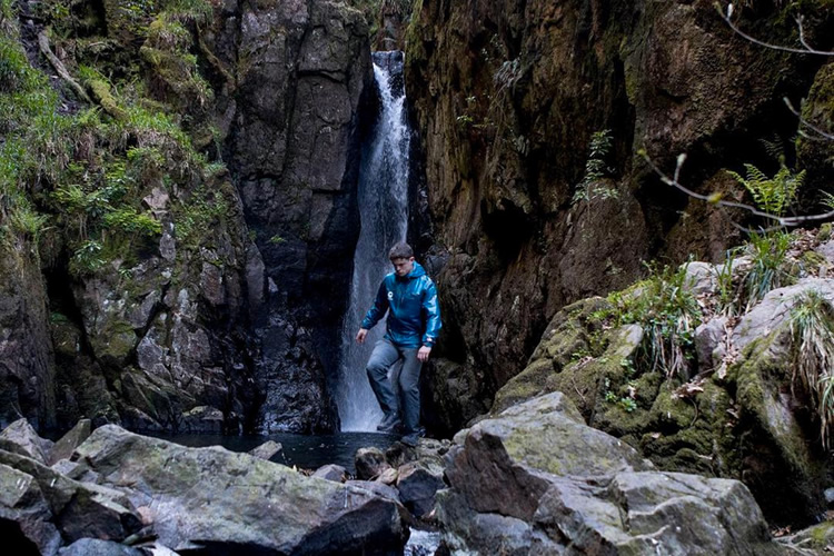 Ranger climbing over rocks in front of a rushing waterfall